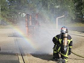 Exercice d'extinction d'incendie avec de l'eau formant un arc-en-ciel